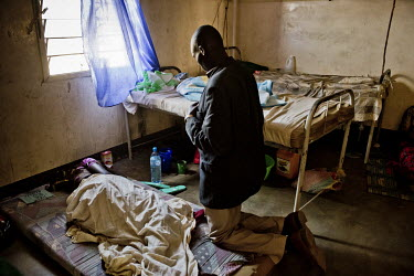 In the Dzaipi health clinic's maternity ward, a husband kneels and prays during a visit to see his sick wife.