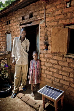 Joshua Matagala and his daughter outside their home with the solar panel for a phone charger he uses to charge phones for customers in order to get an income.