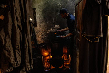 A man adds a powder dye to a solution in a traditional dyer's workshop in the medina.