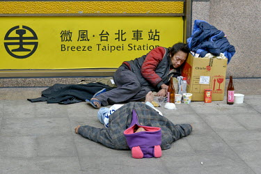 Homeless people, drunk after drinking 'Mi Jiou' a cheap rice wine usually used for cooking, sleep on the ground on the northern side of Taipei Main Station (Breeze Taipei Station).