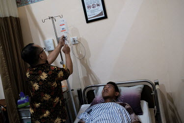 A dose of Tramadol, a painkiller, being injected into Hendik Maret Diasto's intravenous drip bag at Marsudi Waluyo Hospital where he is being treated for a snake bite. Diasto was bitten on the ankle w...
