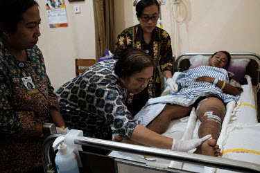 Indonesian snakebite expert, Dr. Tri Maharani, examines Hendik Maret Diasto at Marsudi Waluyo Hospital where he is being treated for a snake bite. Diasto was bitten on the ankle while he and his broth...