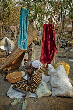 A South Sudanese woman and her child sit among the family's belongings at the Nyumanzi settlement where refugees are being resettled on plots of land. While they wait to be allocated a plot they must...