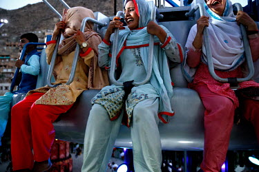 Women enjoy a ride at an amusement park in Kabul City Park during Eid ul Adha.