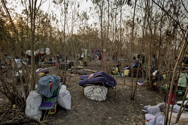 South Sudanese refugees and their belongings piled among the trees at the Nyumanzi settlement as they wait to be resettled on plots of land. While they wait to be allocated a plot they must sleep in t...