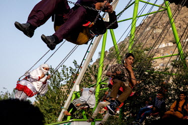 People enjoy a swing ride at an amusement park during the Eid holiday.