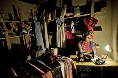 Tailor and dressmaker Robinah Kyayise works in her in workshop in Kirugaluga using the light from a solar lamp she has bought to replace a kerosine one she used previously.