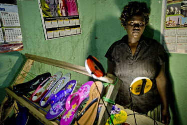 Kyeyune Rashidah stands beside a display of shoes, illuminated by a solar lamp, that she sells from her home in Kirugaluga to suppliment her nurse's income.