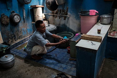 Samijan, a traditional healer, extracting the spinal cord from a spitting cobra in order to add it to a potion for a customer in the kitchen at his family's home in Kediri in East Java, Indonesia on 5...