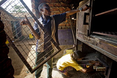 In the Kawempe district of Kampala, Pastor David Kyambadde, director of the Frontier Orphanage and Elderly Home (FOEH) group, puts the shelves into an economical combustion oven while a woman fill it...