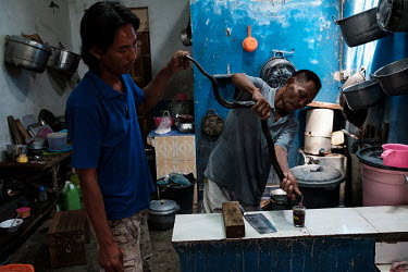 Suprianto and his father, Samijan, draining the blood from a spitting cobra into a potion for a customer in the kitchen at the family's home in Kediri. Samijan is a traditional healer who specialises...
