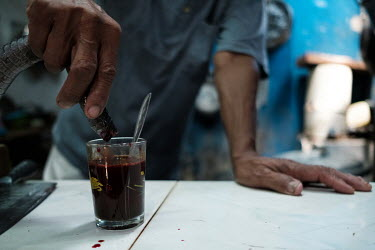 Samijan, a traditional healer, draining the blood from a spitting cobra into a potion for a customer in the kitchen at his family's home in Kediri. Samijan specialises in herbal potions that feature c...