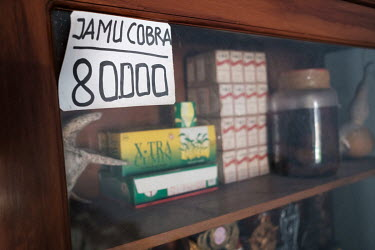 The price of a dose of cobra potion on a cabinet at the home of Samijan, a traditional healer. He specialises in snake potions containing the blood, bile and spinal cord of the snake, as well as wine...