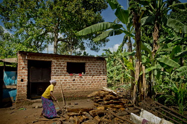 In the Kawempe district of Kampala, a woman belonging to the Frontier Orphanage and Elderly Home (FOEH) group cuts firewood in front of the brick shed in which an economical combustion oven is install...
