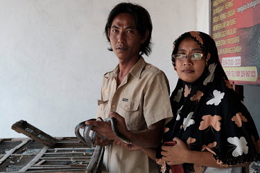 Nanik Sugiarti and her husband, Suprianto, with a spitting cobra at the family home in Kediri. Suprianto's father, Samijan, is a traditional healer who specialises in herbal potions that feature cobra...
