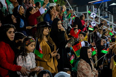Supporters in the women and children section of a stadium during a football match.