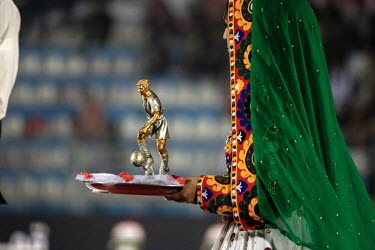 A woman holds a trophy which will be presented to the winning team during a championship match.
