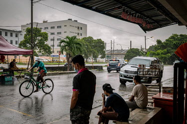 Locals and migrant workers take shelter from the rain beneath shop awnings on a street behind Kossan Rubber Industries Bhd. The company has temporarily suspended operations at one of its plants in Kla...