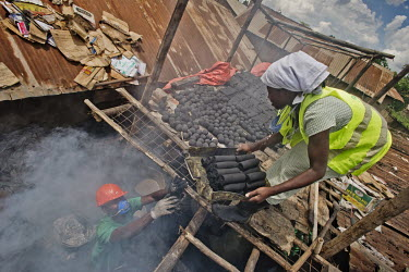 A member of the Lulana Communal Environmentalist's workshop passes a container of briquettes, made from recycled or waste cardboard and used for cooking fuel as an alternative to charcoal or wood, up...