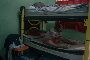 Jose (17), an unaccompanied Honduran migrant, uses his mobile phone on his bed in the unaccompanied minors bedrooms at La 72 shelter. He had to stop studying because his grandmother could no longer su...