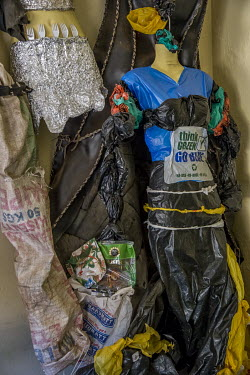 In the workshop and showroom of the artistic collective Afrika Arts Kollective, an evening dress made of blue, yellow and black plastic bags is displayed. On its front, thea slogan: 'Think Green, Go b...