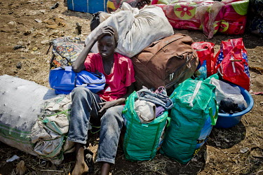 At the Nimule transit centre, on the border with South Sudan, an exhausted young man rests, leaning on his luggage. He came across the border in a private hired truck fleeing fighting in South Sudan.
