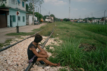 Dulce (16), an unaccompanied Guatemalan migrant, sits on the train tracks where 'La Bestia', or the Beast, passes trough, the train that many migrants have illegally ridden north. Dulce is a transgend...