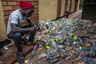 At the feet of a member of the artistic collective Afrika Arts Kollective, who work mainly with waste and recycled objects, dozens of plastic bottles ready to be reused.