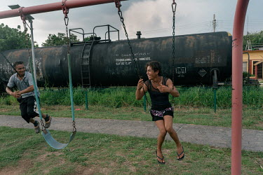 Dulce (16), an unaccompanied Guatemalan migrant, and her friend Jones (32), a Honduran migrant, play on children's swings near some train tracks. Dulce is a transgender woman who left Guatemala for a...