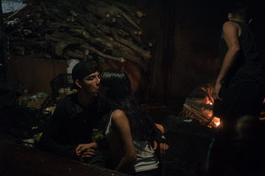 Sonya (17), an unaccompanied Guatemalan migrant, kisses her new boyfriend Cristian (23), a Honduran migrant, in the kitchen of La 72 shelter. A gang member started to go every day to the diner where S...