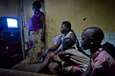 In the living room of their house, lit by a light bulb, the Jackson family watches television, during an outage of UMEME, the national electricity company. Mr Jackson has installed a solar micro-grid,...