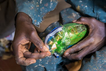 One of the members of the artistic group of Afrika Arts Kollective heats a pair of sandals made from large, flattened plastic soda bottles in a workshop located in the suburb of Naalya.