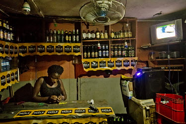 In the Namuwongo 'slum, a woman working behind a bar threads beads as she waits for orders. The bar is equipped with a television to entertain customers and a fan to cool them down. The bar is one of...