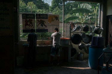 Alan (17), an unaccompanied Guatemalan migrant, washes his dishes at the Casa del Caminante Jtatic Samuel Ruiz Garcia shelter. That morning, he escaped from a bus where Mexican immigration agents were...
