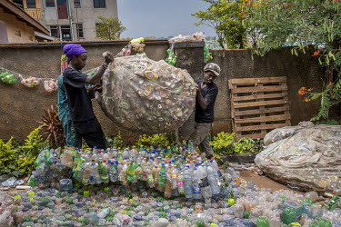 Members of Afrika Arts Kollective carry hundreds of empty cans in a salvaged fisherman's net in a the courtyard of their workshop located in the suburb of Naalya.
