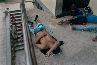 Alan (17), an unaccompanied Guatemalan migrant, takes a nap along other Central American migrants while a nun passes by with migrant children at the Casa del Caminante Jtatic Samuel Ruiz García shelt...