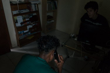 Lionel (17), an unaccompanied Honduran migrant, tries unsuccessfully to call his mother for the first time since he left home to let her know that he is well at the Casa del Caminante Jtatic Samuel Ru...
