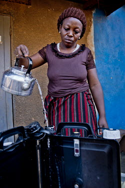 In the district of Kisalosalo, district of Kyebando, in the suburbs of Kampala, Mastulah Nakisozi fills a Solvatten solar water purifier. Nakisozi is part of a group of people infected with HIV who jo...