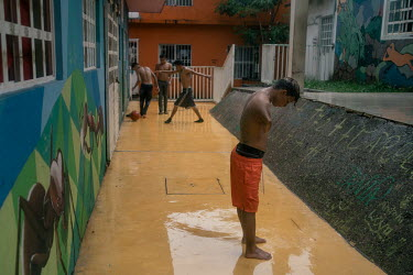 Jose (17), an unaccompanied Honduran migrant, freshens up with rain water while other unaccompanied Central American migrants play at La 72 shelter. He had to stop studying because his grandmother cou...