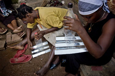 Women make lamps using a plastic soft drinks bottle filled with water and a few drops of bleach and fitted with a metal reflector. They then make a hole in the tin roof of their homes and fit the bott...