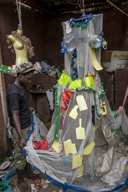 A member of the Afrika Arts Kollective examines the wedding dress created by several visual artists of the movement nusing waste plastic water bottls, a fishing net, and other found materials.