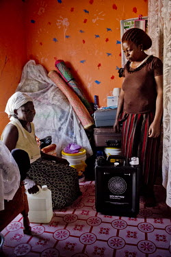 In the district of Kisalosalo, district of Kyebando, in the suburbs of Kampala, Mastulah Nakisozi (R) gives a neighbour water from a Solvatten solar water purifier. Nakisozi is part of a group of peop...