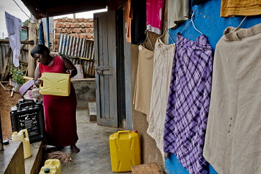 In the district of Kisalosalo, district of Kyebando, in the suburbs of Kampala, a woman fills a Solvatten solar water purifier. She is part of a group of people infected with HIV who joined together t...