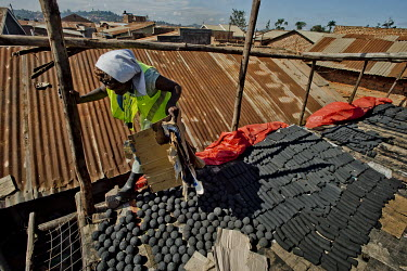 On the roof of the Lulana Communal Environmentalist's workshop, Prosse arranges different types of briquettes, made from recycled or waste cardboard and used for cooking fuel as an alternative to char...