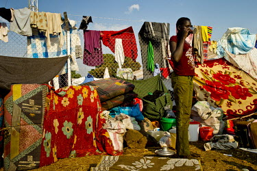 A young South Sudanese refugee drinks water while standing in the place his family has settled, as they wait to be relocated. They have piled up their belongings along the fence which separates Dzaipi...