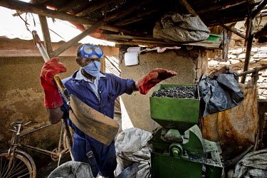 In a backyard workshop, a member of the Lulana Communal Environmentalist group making briquettes for use as cooking fuel, an alternative to charcoal or wood, shreds the raw material, recycled or waste...