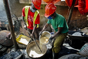 In a backyard workshop, members of the Lulana Communal Environmentalist group mix a binder for the briquettes, used as cooking fuel, an alternative to charcoal or wood, they manufacture from recycled...