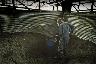 A worker at Green Bio Energy, where they produce fuel briquettes based on agricultural residues and leftover coal, shovels coal dust into a container for use in their manufacturing process. The brique...