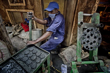 In the Lulana Communal Environmentalist group's backyard workshop, a member shapes briquettes, made from recycled or waste cardboard and used for cooking fuel as an alternative to charcoal or wood, in...