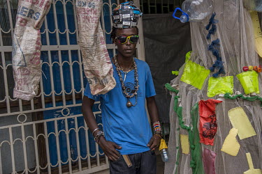 Gisa Jr Gong Brian, an artist from the Afrika Arts Kollective, with some of his clothing creations made from waste.